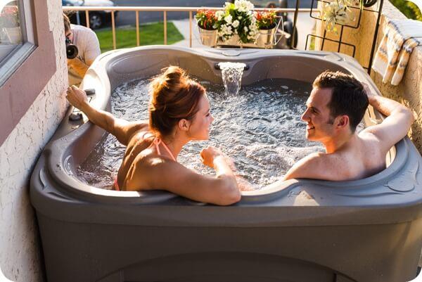 couple enjoying their portable spa in their backyard