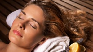 Improve your mental health with a sauna, like this woman laying down with her eyes closed and head on a towel.