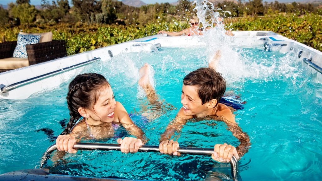 Two kids enjoying spring break in their backyard with an Endless Pools® Fitness System.