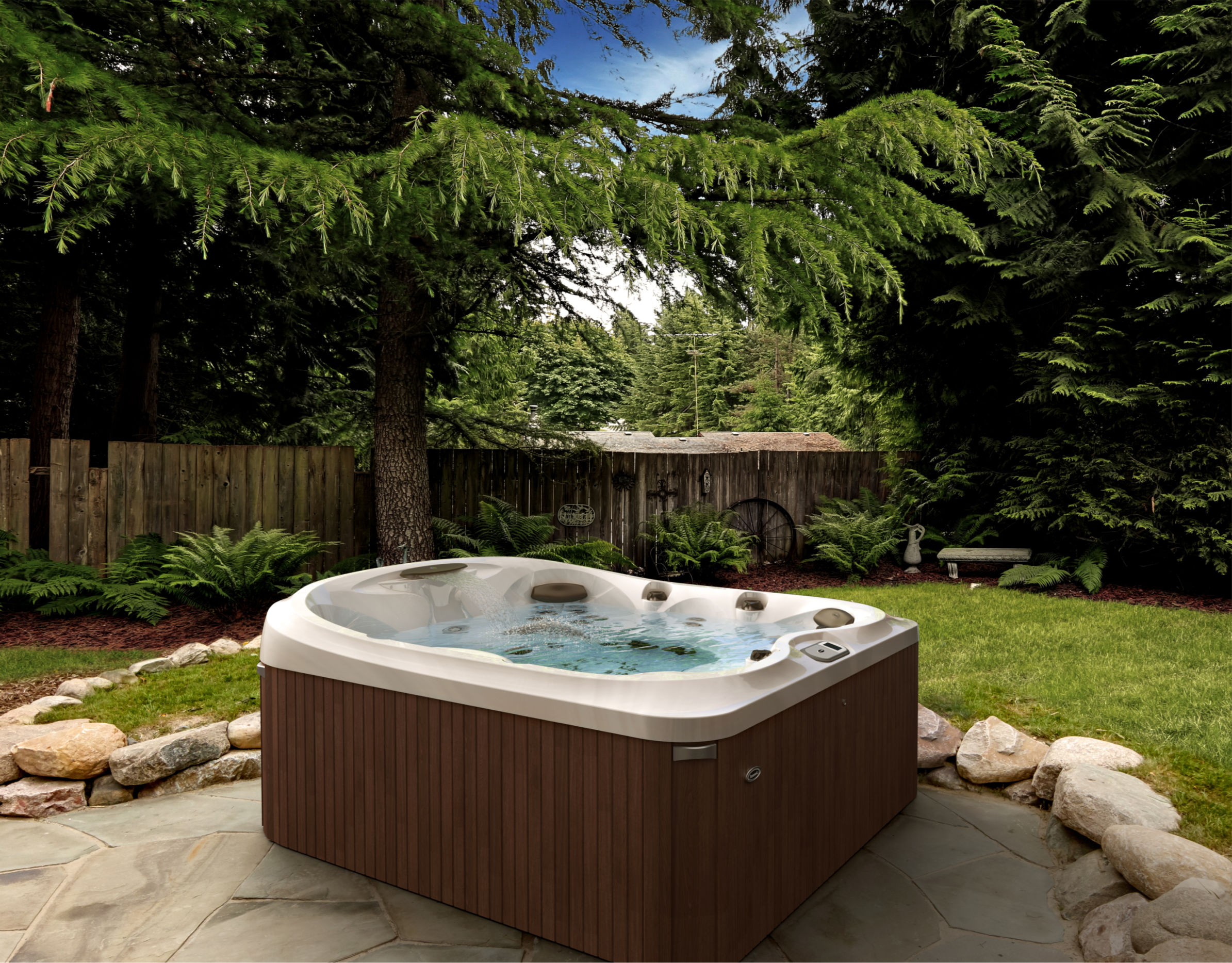 A Jacuzzi® hot tub on a pavemented base in a scenic backyard.