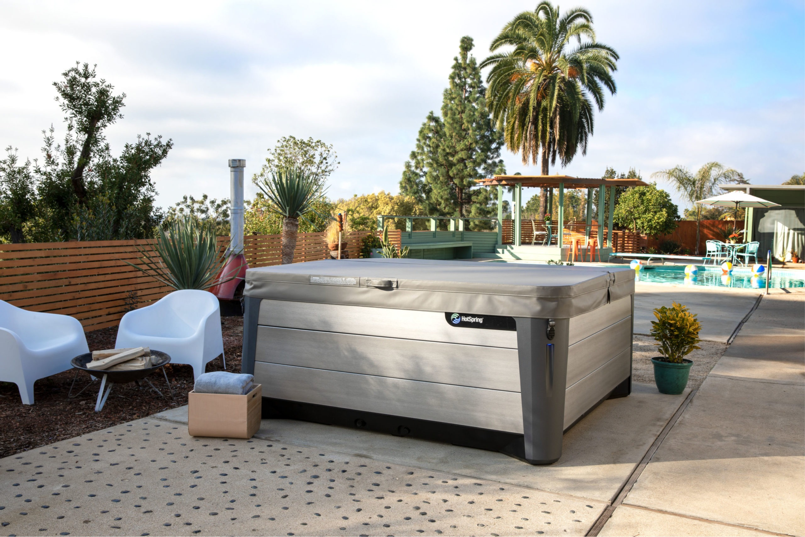 A HotSpring® hot tub installation in the backyard with a cover.