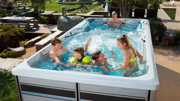 A family using the underwater treadmill and rowing kit, two accessories available for your Endless Pools